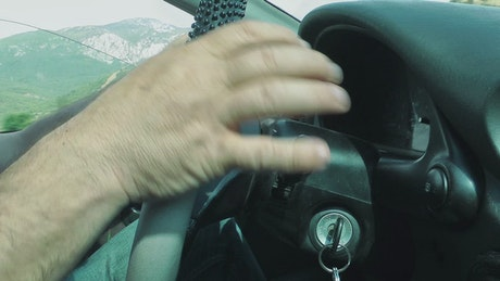 Car driver activating windshield wipers