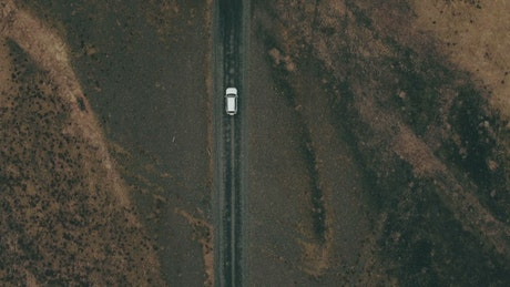 Car driving alone down an empty road