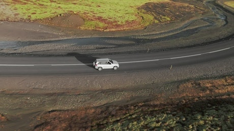 Car driving down a curving road