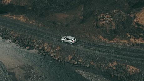 Car following a shallow river