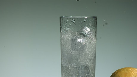Carbonated water falling into a glass