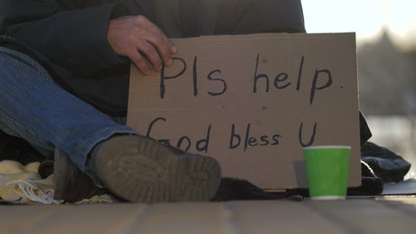 Cardboard sign of a homeless man on the street