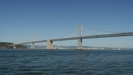 Cargo ship and Sailboat crossing under the bridge