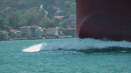 Cargo ship breaking through the water while sailing