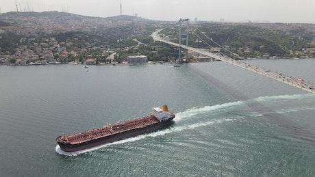 Cargo ship crossing a bridge on a river