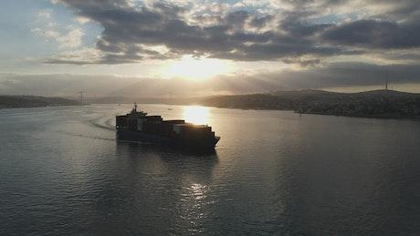 Cargo ship sailing at dusk