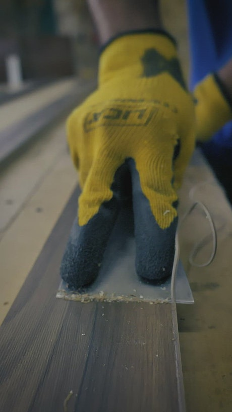 Carpenter cutting down a board with a putty knife