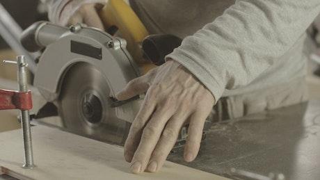 Carpenter cutting through wood