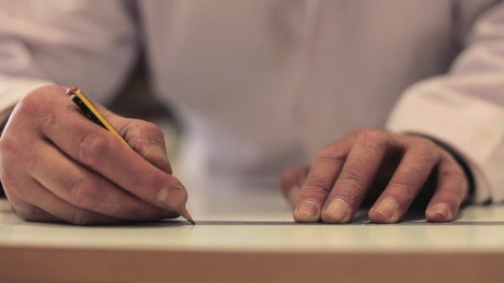 Carpenter marking wood with a pencil
