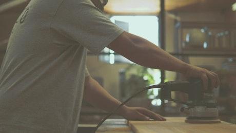 Carpenter sanding a piece of lumber
