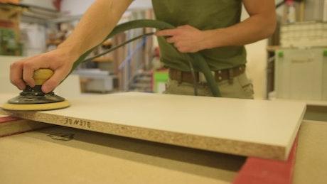 Carpenter sanding a table seen close