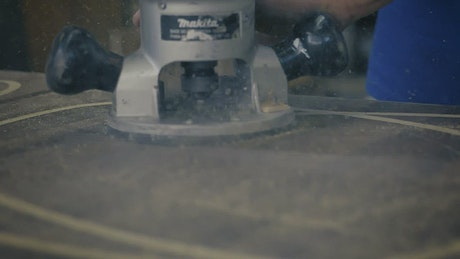 Carpenter sanding with a power tool
