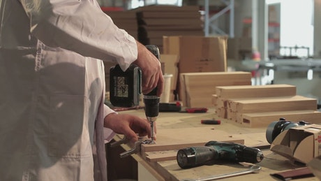Carpenter using an electric drill