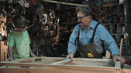 Carpenter with grandson making a window