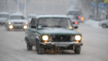 Cars driving along a snow covered street