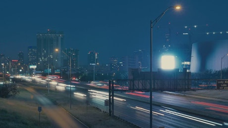Cars traveling on a highway in a city at night