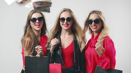 Cash falling around beautiful blonde shoppers