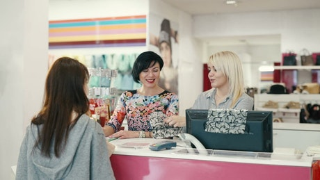 Cashiers smile at customer paying in fashion store