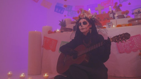 Catrina playing guitar at an altar of the dead