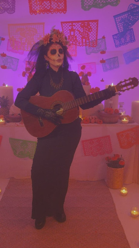 Catrina singing with guitar at an altar of the dead