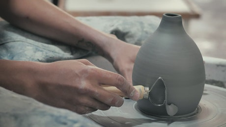 Ceramic artist with clay tool
