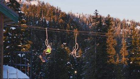 Chairlift on a snowy mountain full of pine trees