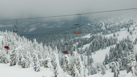 Chairlifts going fast on a snowy mountain