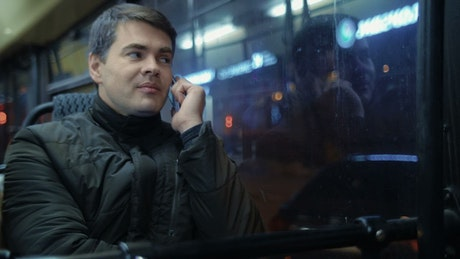 Chatting on the phone on a night bus