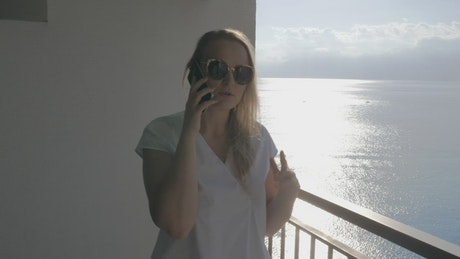Chatting on the phone while standing on a balcony
