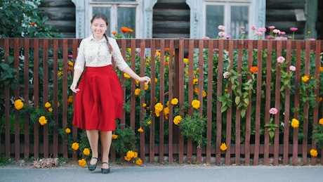 Cheerful girl dancing in front of a garden fence