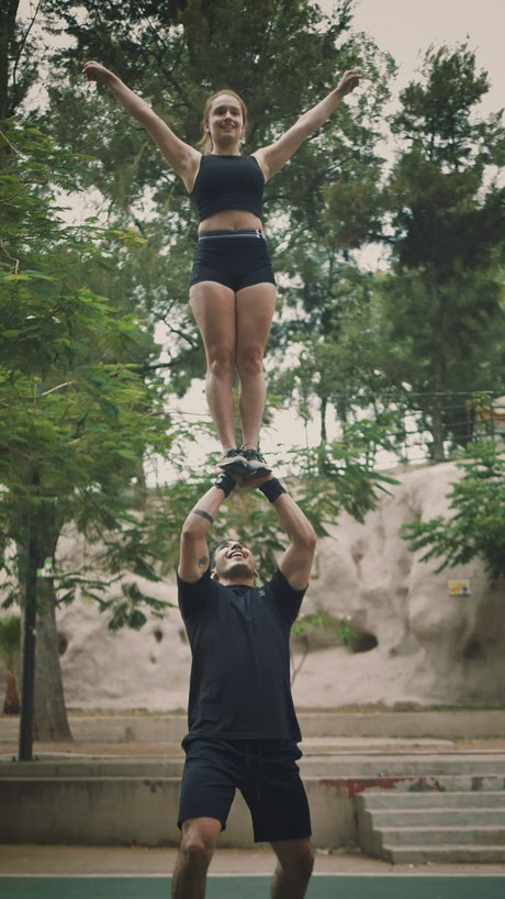 Cheerleader boy catching his partner after a pyramid