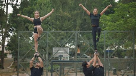 Cheerleaders training pyramid formation outdoors