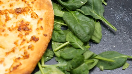 Cheese pizza with salad leaves