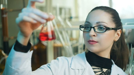Chemistry shaking a conical flask with red liquid
