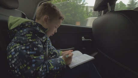 Child doing a puzzle in the car