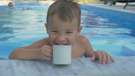 Child drinking from a cup in the pool