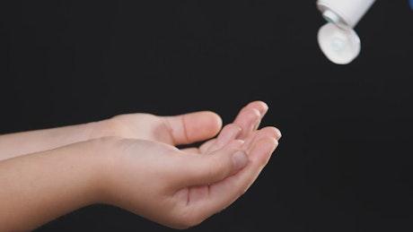 Child hands using hand sanitizer