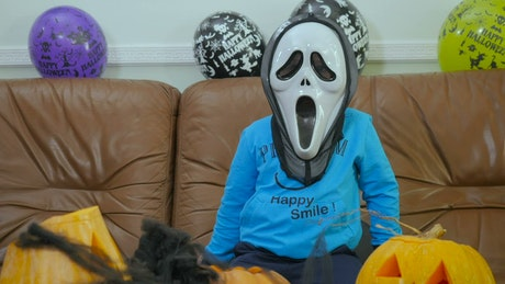 Child in Scream halloween mask makes spooky hand gestures