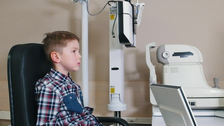 Child putting his eyesight on an eye test device