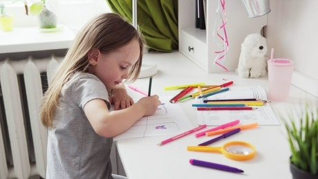 Child sitting at her desk drawing