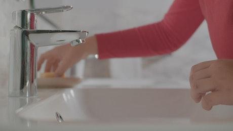 Child washing their hands in a bathroom