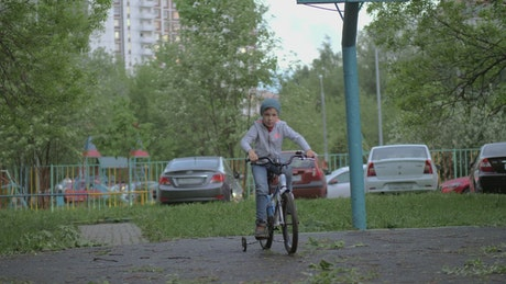 Child with training wheels on their bike