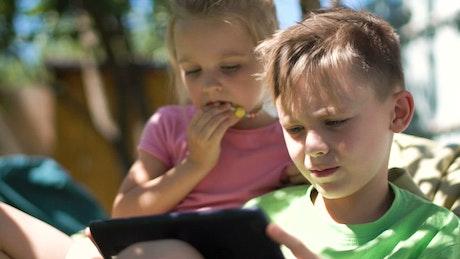 Children enjoying the tablet in the backyard