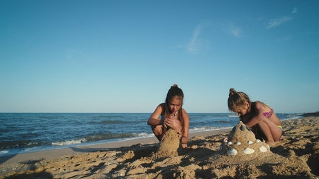 Children forming sand pyramids on the beach