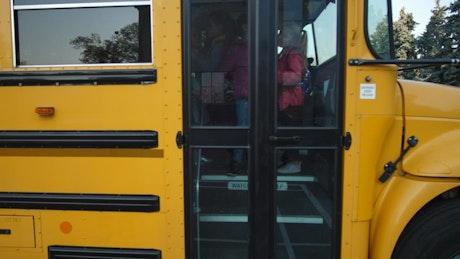 Children getting off a yellow school bus