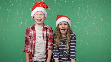 Children in festive hats throwing confetti