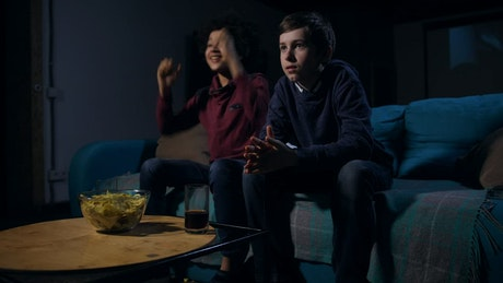 Children on a sofa with snacks watching a movie