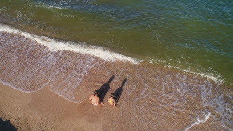 Children playing in the seashore, top aerial shot