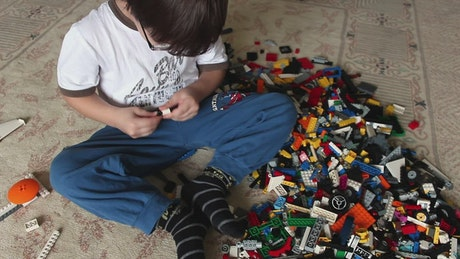Children playing on the floor with lego cubes