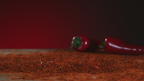 Chili pepper falling into red powder